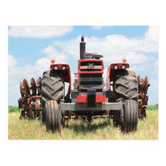 Alter großer Traktor-sitzender Leerlauf an einem Postkarte