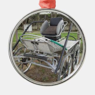 Altmodischer Pferdewagen auf grünem Gras Rundes Silberfarbenes Ornament