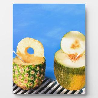 Ananas und Melone tragen mit Strohen am Pool Fotoplatte