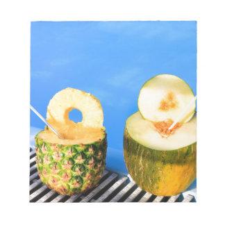 Ananas und Melone tragen mit Strohen am Pool Notizblock
