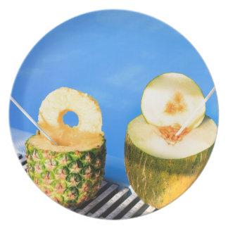 Ananas und Melone tragen mit Strohen am Pool Teller