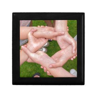 Arme mit den Händen der Mädchen, die sich halten Erinnerungskiste
