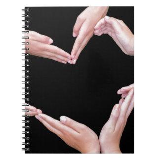 Arme und Hände der Mädchen, die Herz machen, Notizblock