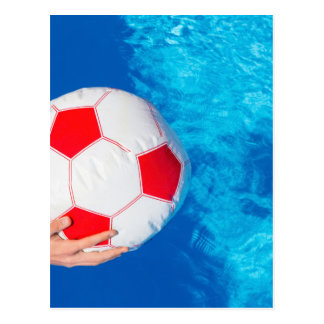 Armholding-Wasserball über Swimmingpoolwasser Postkarte
