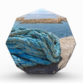 Aufgerolltes blaues Liegeplatzseil am Wasser in Auszeichnung