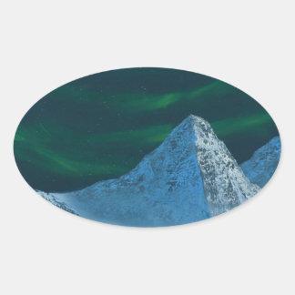 Aurora Borealis über Snowy-Bergen Ovaler Aufkleber