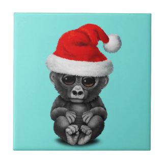Baby-Gorilla, der eine Weihnachtsmannmütze trägt Fliese