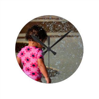 Baby in Rosa eins sie im Brunnen Uhr