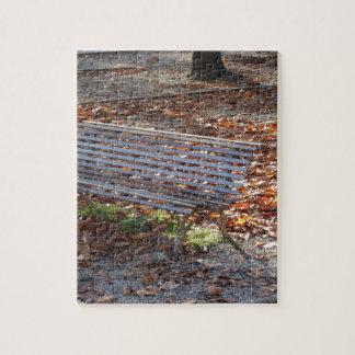 Bank im Herbstpark mit totem Blätter Puzzle