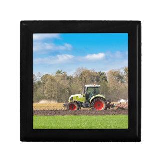 Bauer auf dem Traktor, der sandigen Boden im Erinnerungskiste