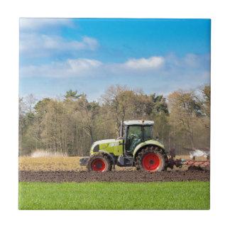 Bauer auf dem Traktor, der sandigen Boden im Fliese
