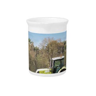 Bauer auf dem Traktor, der sandigen Boden im Krug