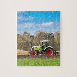 Bauer auf dem Traktor, der sandigen Boden im Puzzle