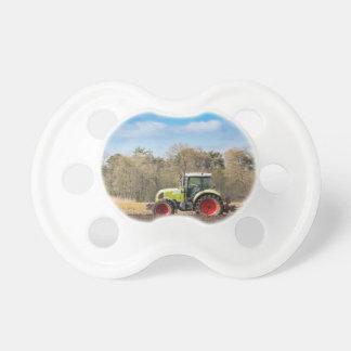 Bauer auf dem Traktor, der sandigen Boden im Schnuller