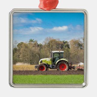 Bauer auf dem Traktor, der sandigen Boden im Silbernes Ornament