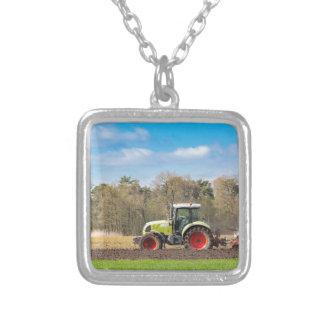 Bauer auf dem Traktor, der sandigen Boden im Versilberte Kette