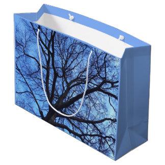 Baum-Überdachung gegen einen blauen Winter-Himmel Große Geschenktüte