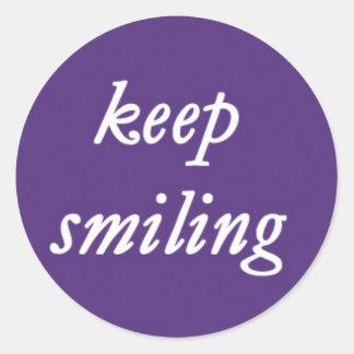 Behalten Sie das Lächeln auf einem lila Runder Aufkleber
