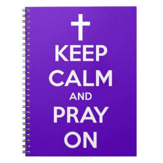 Behalten Sie Ruhe und beten Sie auf lila Notizblock