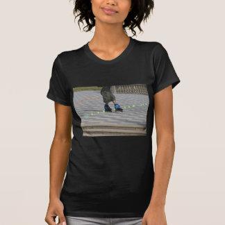 Beine des Typ auf Rollerblades. Rollerblader T-Shirt