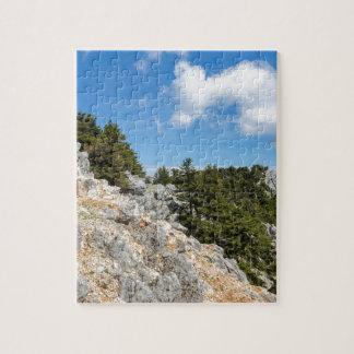 Bench auf felsigem Berg mit Bäumen und blauem Puzzle