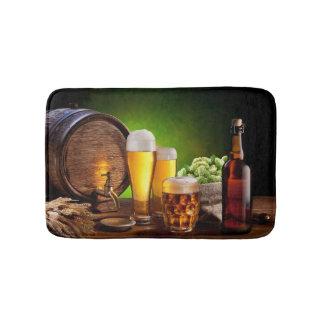 Bierfaß mit Biergläsern auf einer hölzernen Badematte