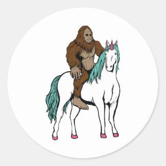 Bigfoot, der ein Einhorn reitet Runder Aufkleber