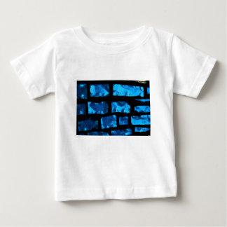 Blaue Glasklumpen mit schwarzem Bewurf zwischen Baby T-shirt