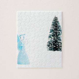 Blauer Glasengel, der nahe Weihnachtsbaum betet Puzzle