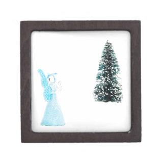 Blauer Glasengel, der nahe Weihnachtsbaum betet Schachtel