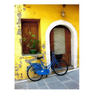 Blaues Fahrrad gegen eine gelbe Wand Postkarten