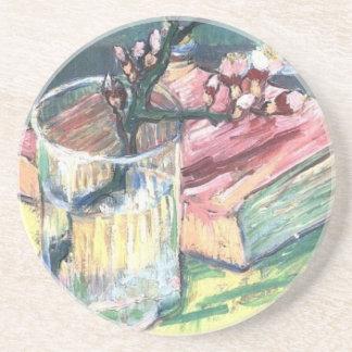 Blühende Mandel verzweigen sich in ein Glas und in Untersetzer