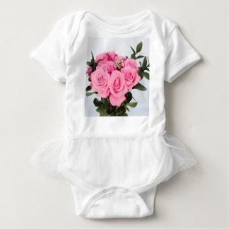 Blumenstrauß der rosa Rosen auf einem weißen Baby Strampler