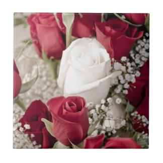 Blumenstrauß der Roter Rosen mit einer weißen Rose Fliese