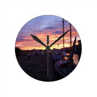 Boote in einem Jachthafen am Sonnenuntergang Runde Wanduhr