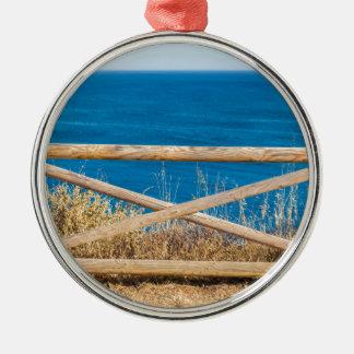 Bretterzaun an der Küste mit blauem sea.JPG Silbernes Ornament