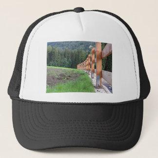 Bretterzaun mit Wald im Hintergrund Truckerkappe