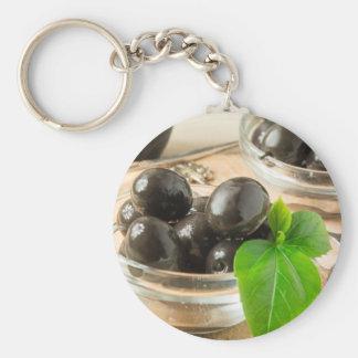 Brown legte Oliven auf dem alten hölzernen Schlüsselanhänger