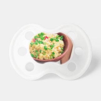Brown-Schüssel mit einem Teil gekochtem Reis Schnuller