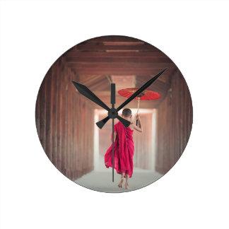 Buddhistischer Mönch mit rotem Regenschirm Runde Wanduhr