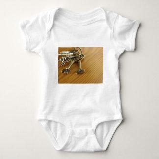 Bündel abgenutzte Hausschlüssel auf hölzerner Baby Strampler