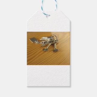 Bündel abgenutzte Hausschlüssel auf hölzerner Geschenkanhänger