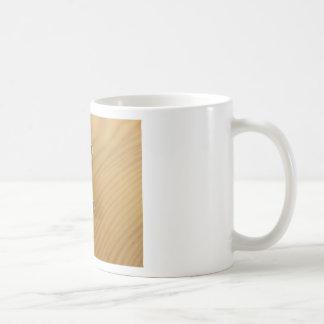 Bündel abgenutzte Hausschlüssel auf hölzerner Kaffeetasse