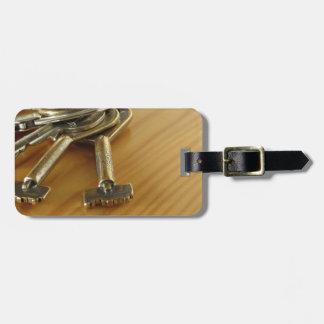 Bündel abgenutzte Hausschlüssel auf hölzerner Kofferanhänger