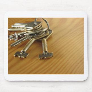 Bündel abgenutzte Hausschlüssel auf hölzerner Mousepad