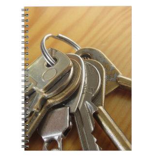 Bündel abgenutzte Hausschlüssel auf hölzerner Notizblock