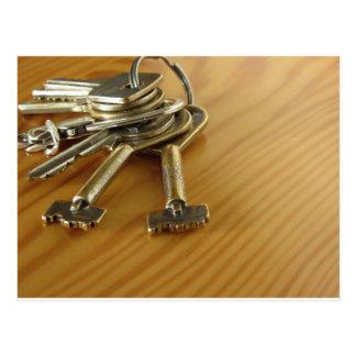 Bündel abgenutzte Hausschlüssel auf hölzerner Postkarte