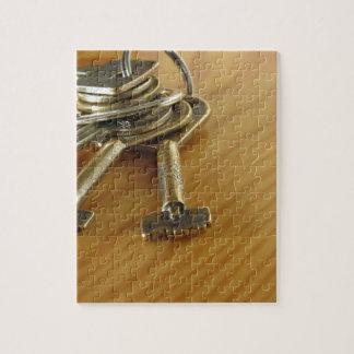 Bündel abgenutzte Hausschlüssel auf hölzerner Puzzle