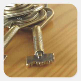 Bündel abgenutzte Hausschlüssel auf hölzerner Quadratischer Aufkleber