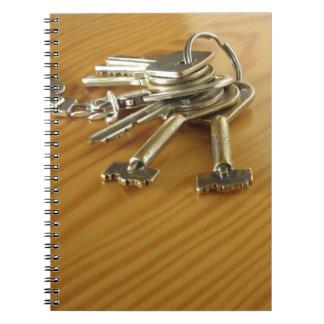 Bündel abgenutzte Hausschlüssel auf hölzerner Spiral Notizblock